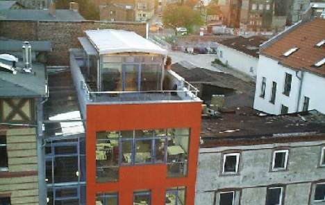 Fenster aus Alu-/Holzkonstruktion, Holzfassade aus Leimholzplatten. Auf Dach gebaut