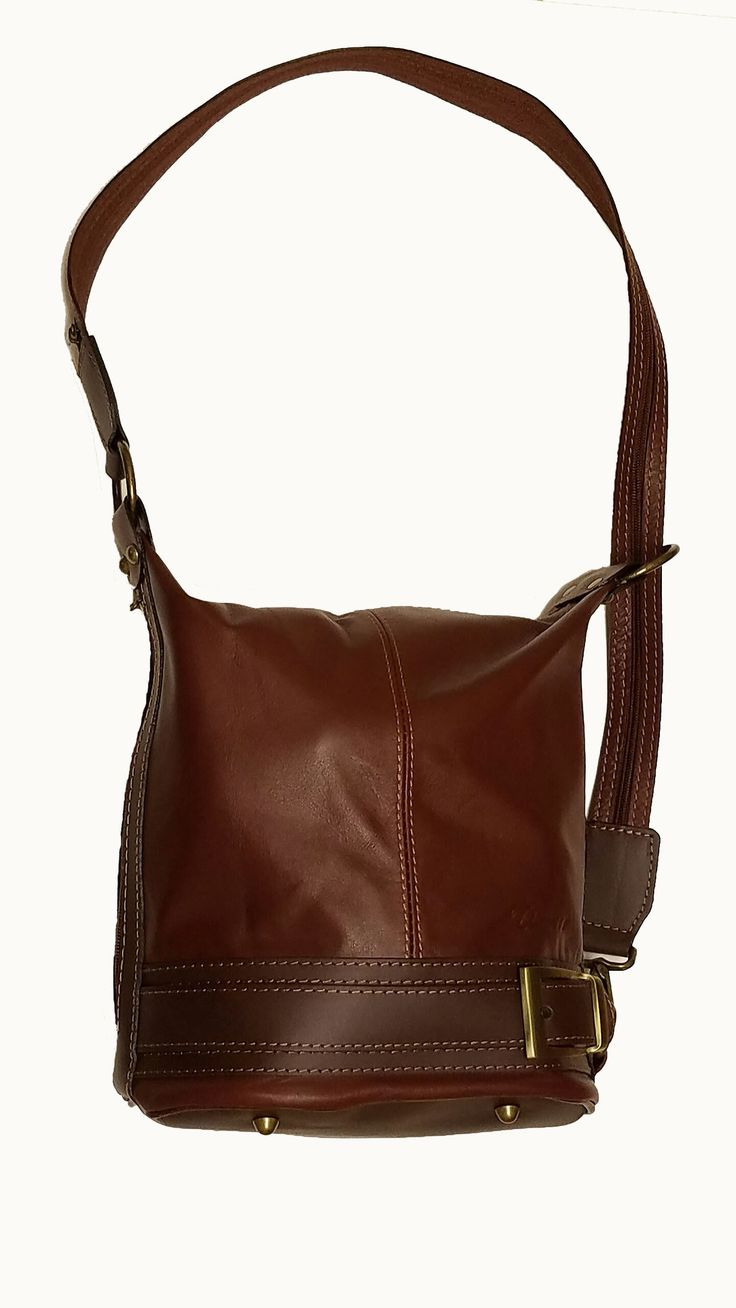 """Genuine soft leather bucket bag convertible into a backpack purse. Zipped pocket inside. Zipped pocket on outside. Buckled belt and four protective metal studs on the bottom. Long zipped strap which converts from shoulder bag to backpack. Strap buckle to upper rings permits use as short cross body bag. This leather handbag is modern and chic. Size: 11""""L x 11""""H x 6.5""""W Shoulder Strap: 34"""" long"""