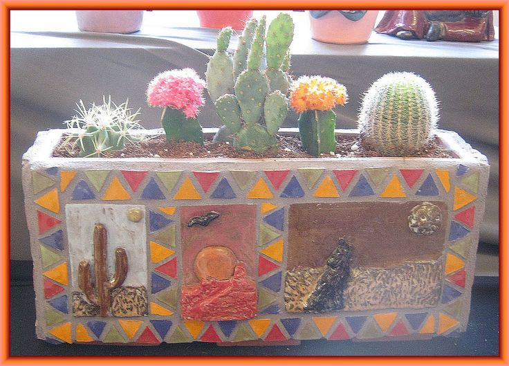 Southwestern planter showing ceramic pictures of a cactus, sunset and coyote with flowering cacti growing in it. An artistic accent to southwestern decor!