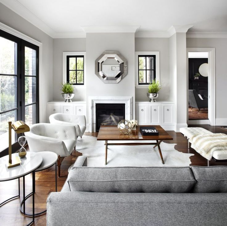 Simplified styling makes a space look more expensive: black window frames, white, marble table, wood, hide rug, fur throw.  Textures combine to make room feel more luxurious.