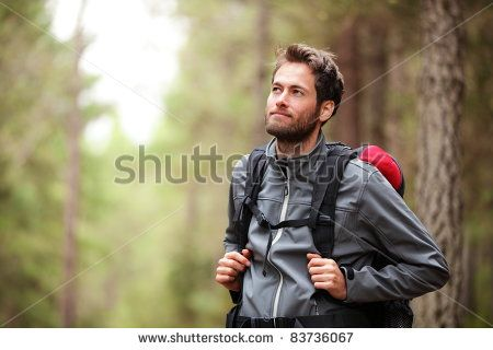 Hiker - man hiking in forest. Male hiker looking to the side walking in forest…