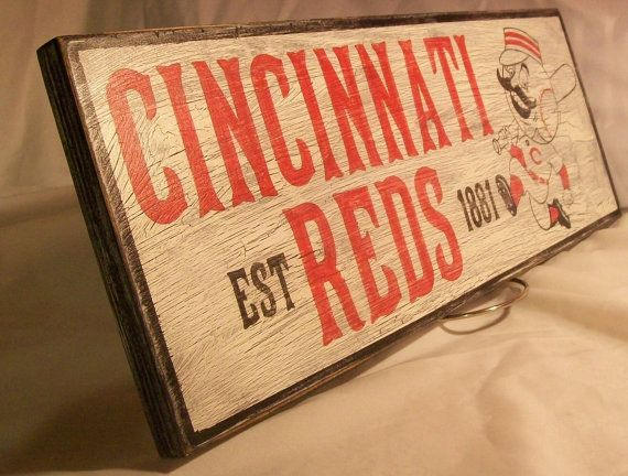 The Cincinnati Reds. This sign is hand painted on cabinet grade birch and measures 6 1/2  x 17 . This sign is hand painted with quality red and