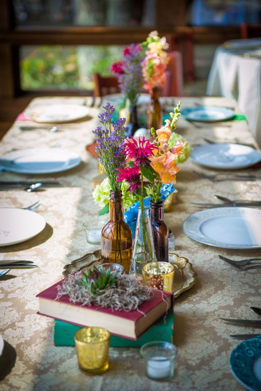 burlap covering, native flowers, different stoneware and china, multi-colored cloth napkins, old books, colored glass, and bird cages.