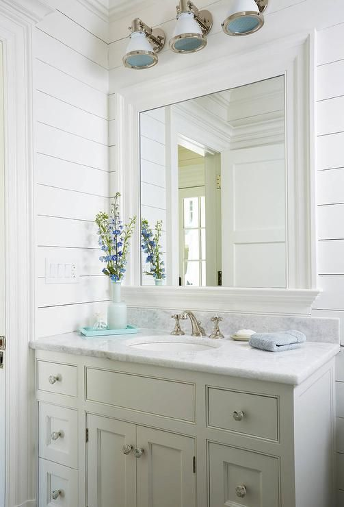 Photos On SINK Gorgeous white beach style bathroom is fitted with industrial wall sconces mounted to a white shiplap wall above white framed mirror with a shelf