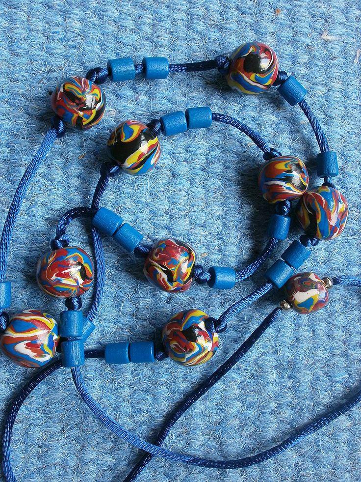 Půlnoční tajemství Náhrdelník - kuličky z fimo hmoty ve veselých barvách (modrá,bílá, červená, žlutá, černá) s modrými dřevěnými korálky bez zapínání.  Průměr kuliček 1,3 cm. Délka náhrdelníku je 40 cm.