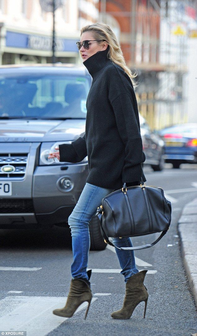 Runway model: The British model kept herself warm in the chilly breeze with a large knitted black high-neck jumper and skintight washed-out denim jeans, while she added height to her svelte frame with an envy-inducing pair of khaki suede ankle boots