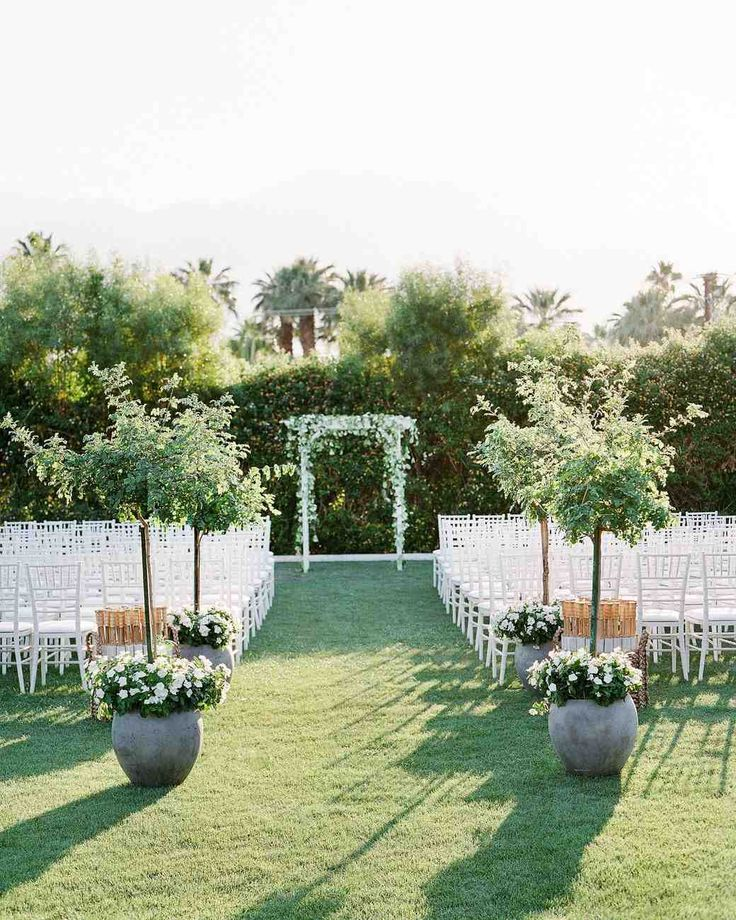A Casual, Outdoor Wedding in Palm Springs with a Black-Tie Dress Code | Martha Stewart Weddings - The ceremony was held on the property's Gene Autry lawn, where rows of white chairs, potted green plants at the beginning of the aisle, and a white arch covered in greenery made up the quintessential outdoor nuptials set-up.