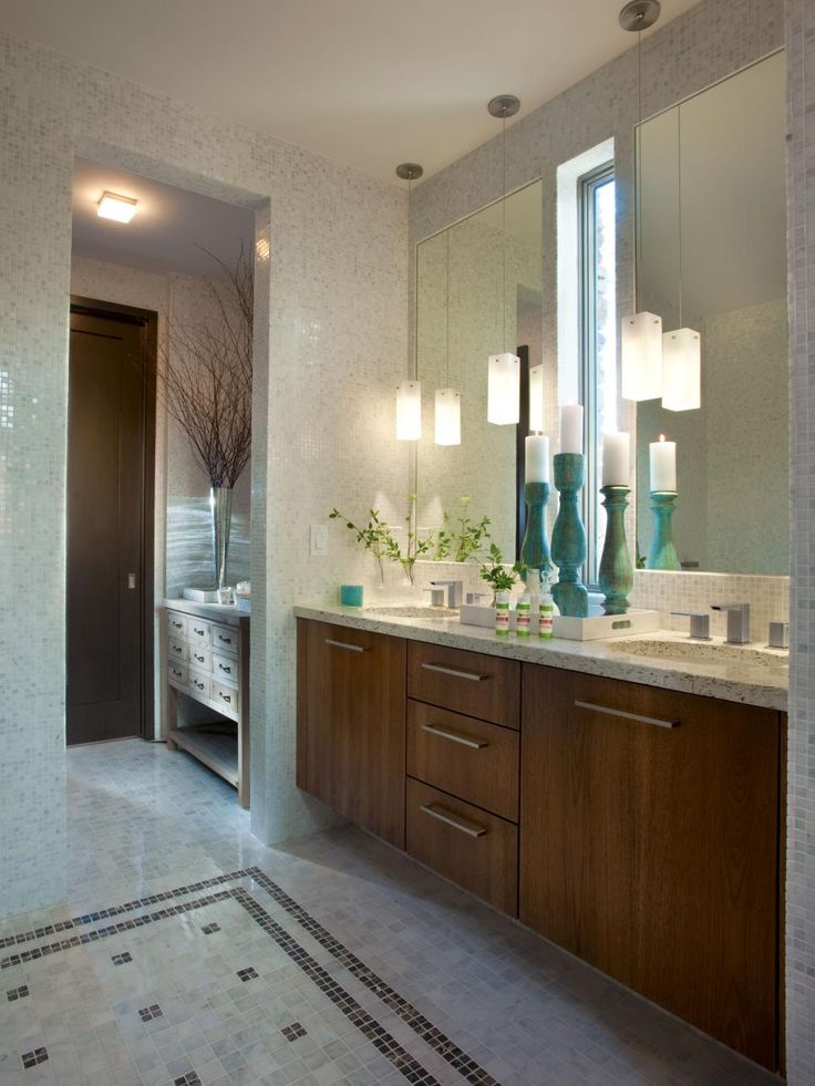 A contemporary hickory wood vanity accommodates his and hers sinks and tall rectilinear glass pendant lights that echo the design of the sliver windows in the master bathroom of the HGTV Green Home 2012.