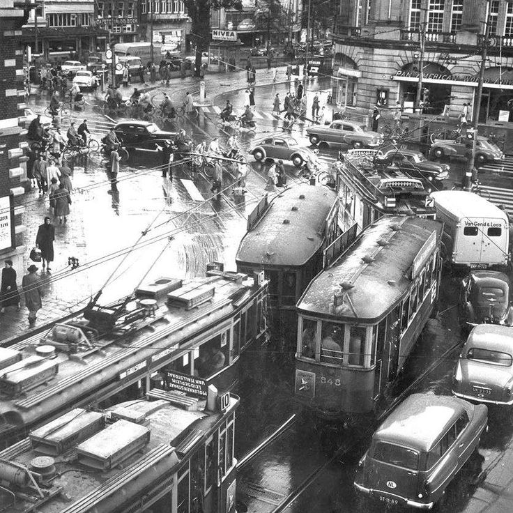 1957. A view of the Leidseplein in Amsterdam during rush hour on a rainy day. The Leidseplein is a square located at the southwest side of the main canal area. It is, and has been for decades, a busy meeting place and nightlife area. Today, foot and bike travel passes through the square and car access is limited. The Stadsschouwburg and the nearby American Hotel, are the most notable architectural landmarks on the square. #amsterdam #1957 #Leidseplein