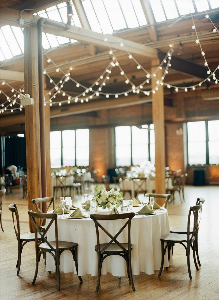 {{White table and string lights for spring wedding at Bridgeport Skyline Loft in Chicago.}} Photography by Britta Marie Photography http://brittamariephotography.com/    Flowers by Pollen, pollenfloraldesign.com