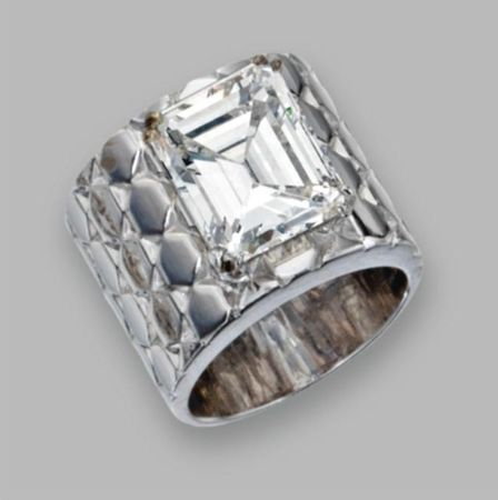 18 Karat White Gold And Diamond Ring The emerald-cut diamond weighing 6.47 carats, within a wide white gold band enhanced by geometric motifs