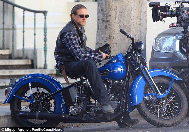 Sweet ride: Charlie was spotted on a shiny blue motorcycle while filming outside a courthouse