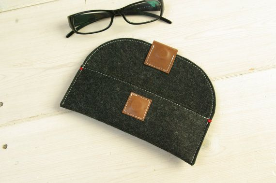 A felt case to hold your glasses, pens or make-up. The strong magnetic closure is covered with buffalo leather. Small red details at the top corners. Size. Inside measures: 6 x 17 cm - 2.36 x 6.7 inch. 100% merino wool felt protects from bumps and scratches Warm brown leather closure. Vegetable tan leather / Undyed Felted wool / Made in Holland Colour. 3 colors undyed wool From top to bottom in the first picture: black - grey - sand brown Items usually take 5-7 business days to b...