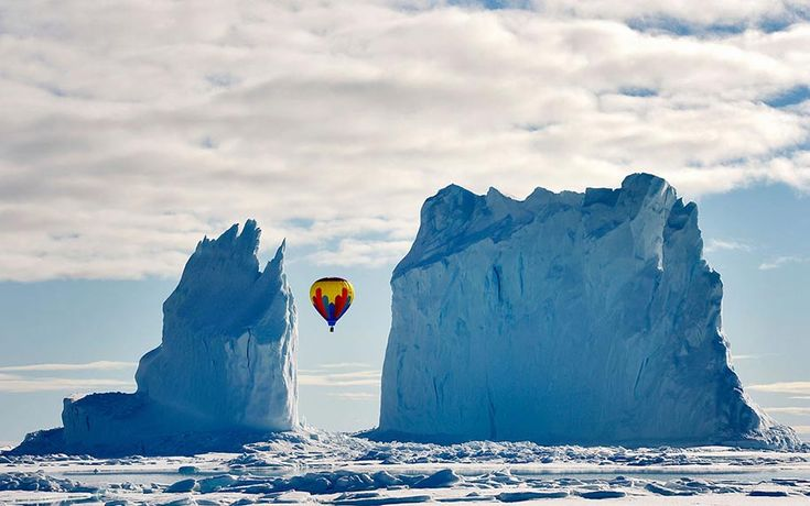 "Michelle Valberg  ""This photo was taken on the ice near Arctic Bay last month. As far as we know, it is the highest latitude passenger flight on a hot air balloon ever. It was quite the sight to see a hot air balloon fly between the iceberg columns — it is one iceberg but looks like two."""