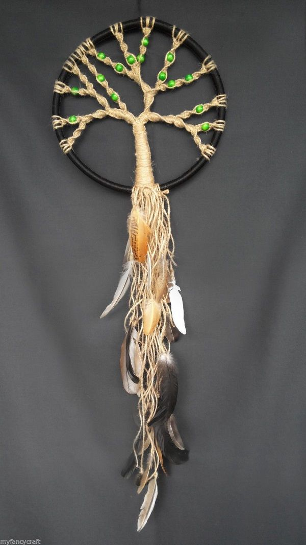 Unlike the loop of strings, this one resembles more of a tree with beads in the branches reaching up to the circle. Then the roots are made of the string as well with feathers attached.