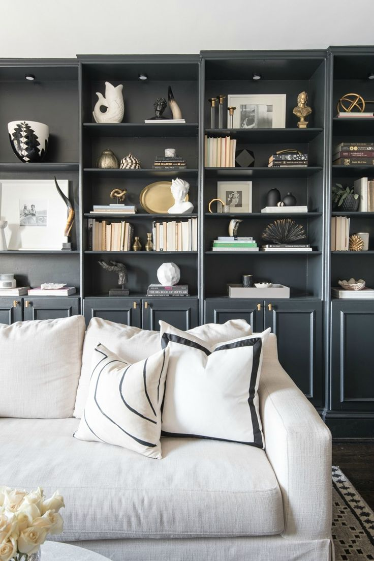Library + Bookshelf Decorating Ideas. White sofa, black and white pillows, dark grey bookshelves. Shannon Claire Interiors.