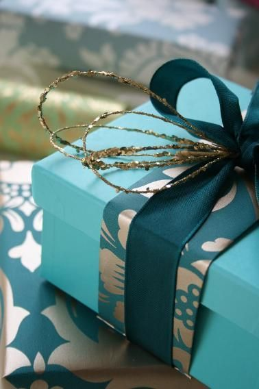 Tiffany blue colored box wrapped in a narrow band of turquoise and gold wrapping paper. Accented with sparkly gold wire.