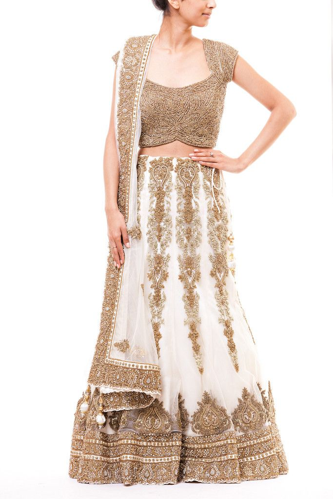 White 10 panel net lehenga with gold french knots and zardozi embroidery highlighted with topaz crystals. This lehenga comes with a fully crystallized topaz crop top with cap sleeves.