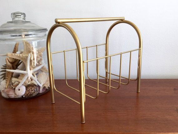Brass Magazine Towel Rack / Mid Century Hollywood Regency Gold Tone Multipurpose Rack / Brass Metal Book Bathroom Organizer / Record Holder  Vintage midcentury metal multipurpose rack with brass gold tone color Can be used for magazines, books, towels, records.... Sturdy, strong, and in excellent condition  Measures: 13 wide 11.5 tall 7.25 deep  CONDITION REFERENCE CHART RATING: Excellent normal light wear for age  Thanks for looking and check out my other listings at…