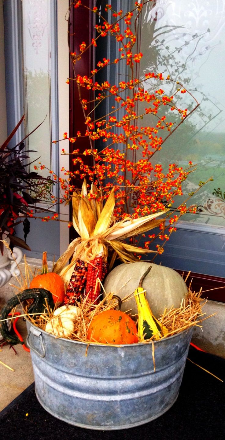 beautiful porch decor made with an old washtub filled with products of autumns harvest and bittersweet - Harvest Decorations