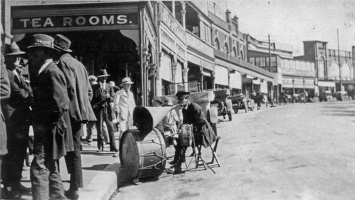Main St Katoomba. Behind the musician is The Niagara Cafe, still operating. The chemist shop is the site of Katoomba's first pharmicist, John Duncan (1887). Became Medlicott Bros Pharmacy (1905) - the building facade is still intact. Later operated by EW Thomas of the Greenwell & Thomas Pharmacy (1930's to 1950's), this business name still survives as a pharmacy in Katoomba Street. The Kodak sign indicates the photo business of Charles Kitch & Co. The cars appear to be Model T Fords. 1922