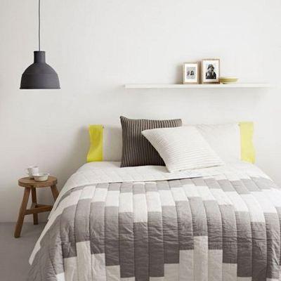 Cama con edredón geométrico #decoración #invierno #minimalista #amarillo #cojín #taburete