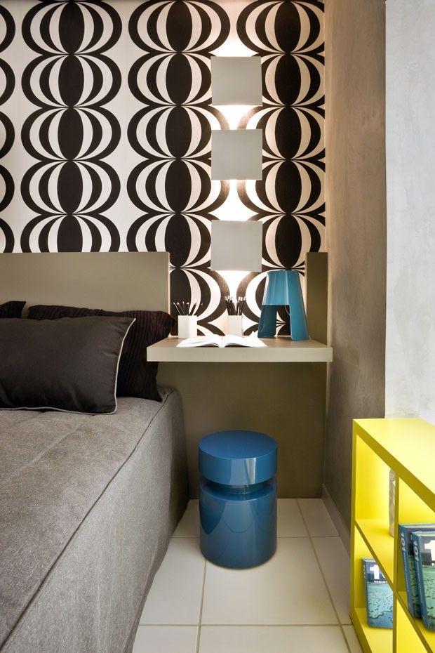 Apartamento pequeno inspirado na Pop Art. O quarto tem papel de parede geométrico e otimização de espaço com móveis multifuncionais.