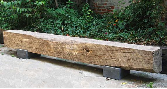 Beautiful wood beam bench on concrete supports.