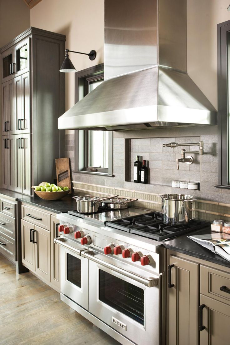 A small niche behind the stove is a great place for oils and spices, and a faucet above the stove is ideal for filling large pots. A mix of grays and browns makes this high-end, custom kitchen feel earthy and natural.