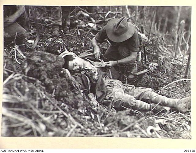 WEWAK AREA, NEW GUINEA, 1945-06-27. PTE V.R. MAURER, INTELLIGENCE SECTION, 2/8 INFANTRY BATTALION, SEARCHING A DEAD JAPANESE SOLDIER FOR DOCUMENTS.