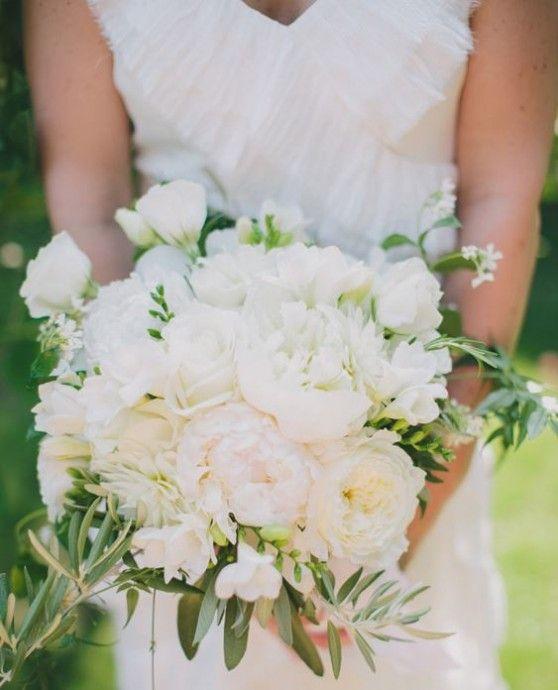 La douceur s'invite à la cérémonie avec une sélection de fleurs rondes d'une blancheur parfaite, ourlée de branchages verts, symbole de prospérité.