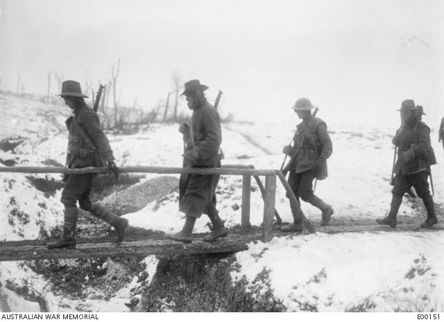 WWI, Jan 1917; Australian soldiers cross a foot bridge over an old trench at Mametz, France.