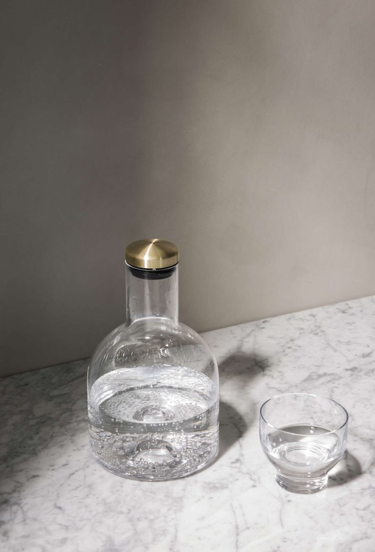 Bottle carafe 1.4l (wide)   Simon James Design    Designed by Norm Architects    The latest addition to the Menu Glass Carafe family, is the 1.4L Bottle Carafe inspired by traditonal brandy and rum bottles with its stout, base. The modern brass lid with a silicone seal will keep liquids fresh and the minimalist, refined form is sculpted from thick-walled mouth-blown glass.