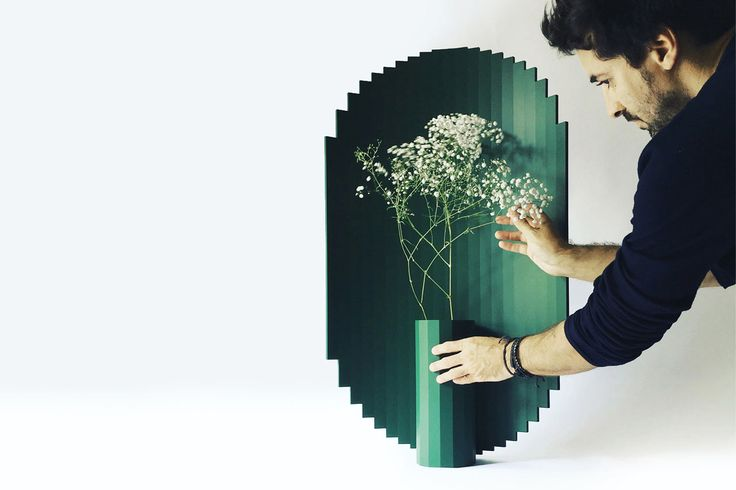 Corian vases that invite you to present flower arrangements that feel partially protected by the digital-like shield behind them.