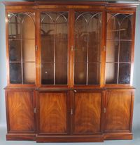 """A George III style mahogany breakfront library bookcase, having moulded cornice above a pair of lancet bar glazed doors  enclosing adjustable shelves with a further 4 fielded panelled  cupboard doors below, raised on a plinth base 88""""h x 85""""w x  19""""d  SOLD FOR £540"""