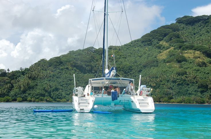 One of TSCH's catamarans anchored in front of one of French Polynesia's islands. Sail in French Polynesia aboard a catamaran and live the DREAM!  #chartercatamaranfrenchpolynesia #yachtcharterfrenchpolynesia #frenchpolynesia #visitfrenchpolynesia #sailingfrenchpolynesia #sailingholidayfrenchpolynesia