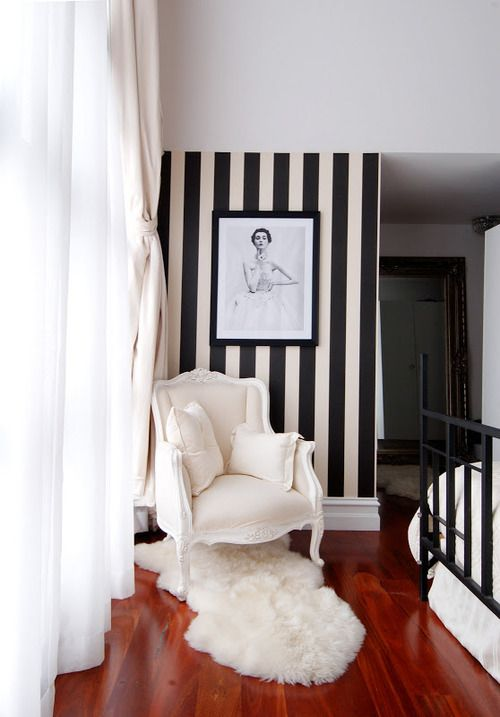This is such a plush and sophisticated area with the black and white striped wallpaper, white chair and fur rug