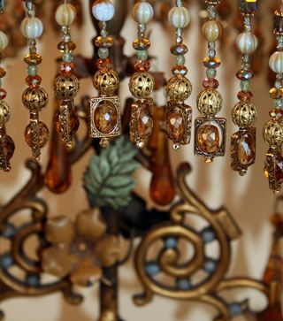 Ornate antique table lamp with original paint and wonderful amber prisms holds a custom Chinoiserie Bird lampshade dyed deep amber to dusty midnight blue. The lamp is covered in an array of vintage textiles with Oriental motifs: cream on black net silk lace and gold metallic embroidered netting overlaid with vintage bird appliqués. Vintage gold trim and hand beaded glass and crystal fringe adorn the bottom of the shade.