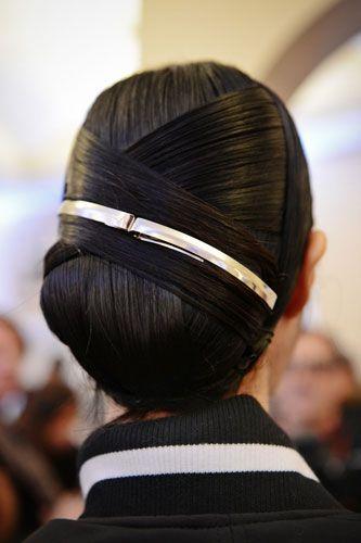 At first glance, this look could be a simple side chignon, but the close-up view shows that it's anything but basic. Working with Kérastase Ciment Thermique to get that super-slick texture, stylist Odile Gilbert created this Art Deco-inspired look, wrapping sections of hair over each other. The two silver barrettes add even more slick, modern texture.