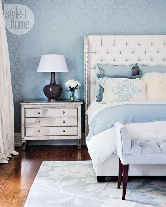 Pastel blue master bedroom. The blue damask wallpaper creates a soft backdrop for the button-tufted headboard and the mirrored nightstand adds a hint of glamour.