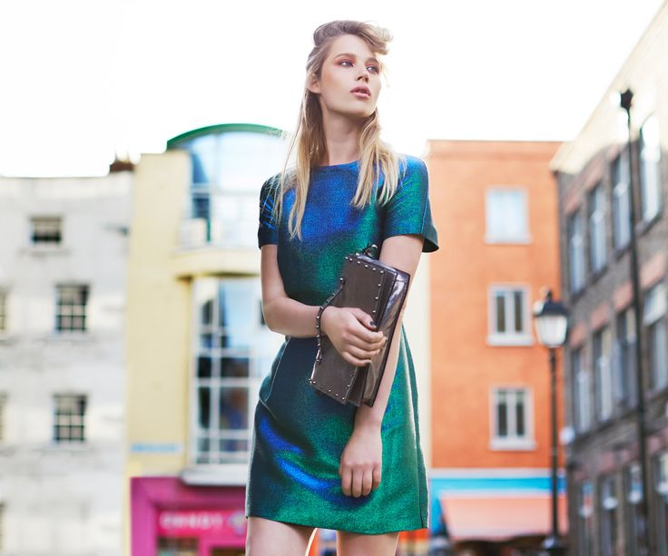 Metallic short-sleeved dress by Savida in green and blue tones, paired with Savida studded clutch