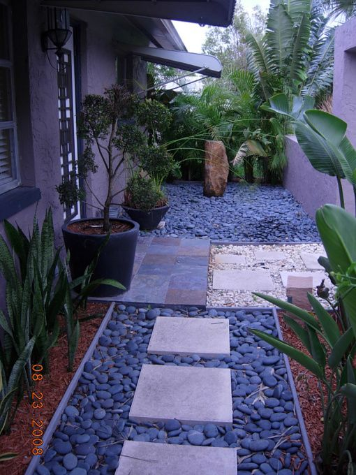 Modern oasis with asian influence, The ground is covered in mexican beach pebbles with a walkway of tile squares.