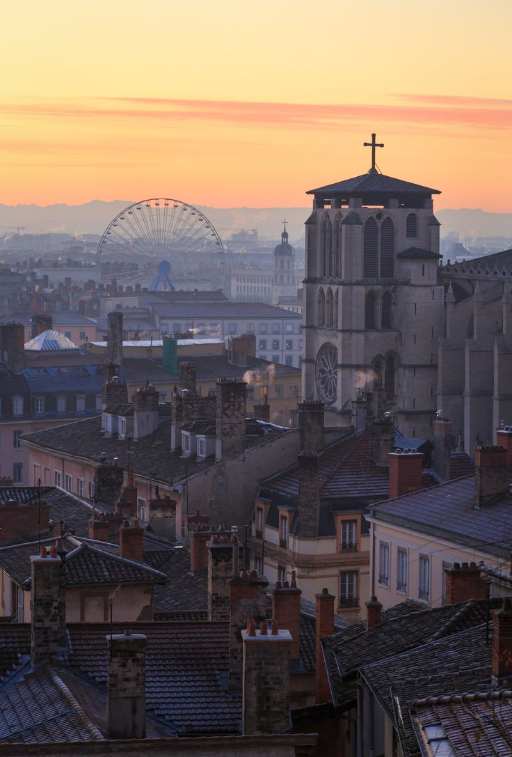 Saint-Jean-Baptiste - Second in a serie of three: Cathedral Saint-Jean-Baptiste in Vieux Lyon and the Ferris wheel at Place Bellecour in Lyon during a colorful dawn in december.