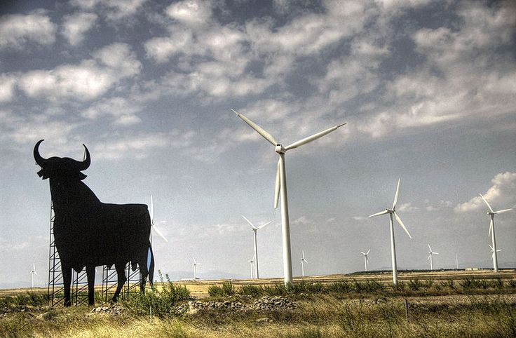 Windmills are typically installed in favourable windy locations. In the image, wind power generators in Spain, near an Osborne bull.