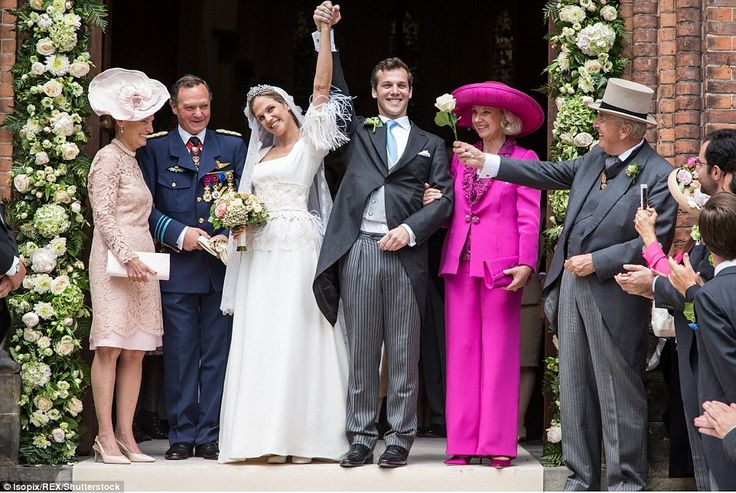 The triumphant couple lifted their arms as they posed outside St Peter's Church with their parents