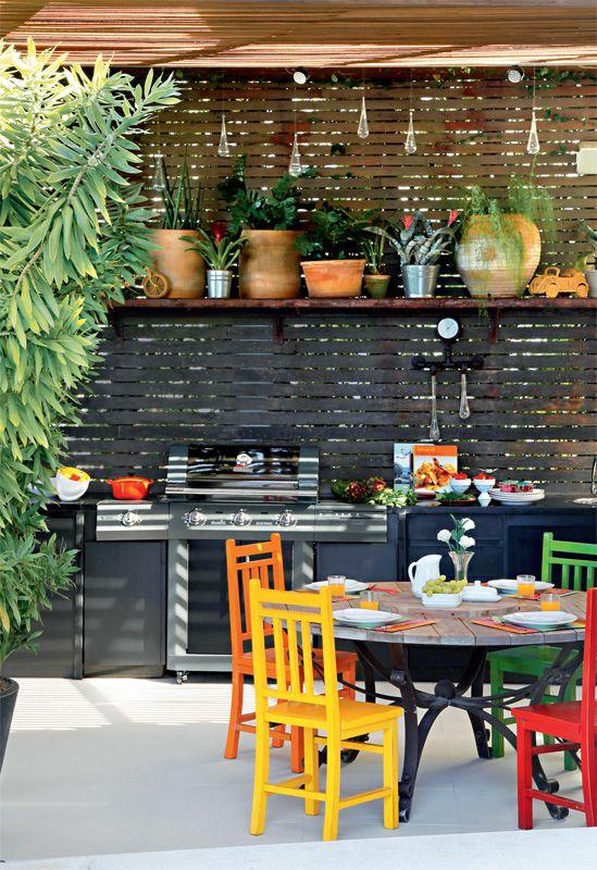 """Cercada por cadeiras coloridas, a mesa redonda não prejudica a circulação. Na parede do forno de pizza, os azulejos da Pavão Revestimentos (Mediterrani) desenham um mosaico. """"Adoro estampa e cor"""", diz Marcelo."""