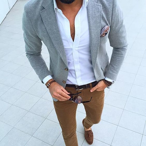 Rock a grey blazer jacket with cognac chinos to create a smart casual look. Brown suede tassel loafers will instantly smarten up even the laziest of looks.   Shop this look on Lookastic: https://lookastic.com/men/looks/blazer-long-sleeve-shirt-chinos/21029   — Grey Blazer  — Red Paisley Silk Pocket Square  — White Long Sleeve Shirt  — Tobacco Chinos  — Brown Suede Tassel Loafers