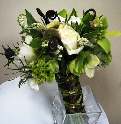 bouquet made with peonies, lily of the valley, fiddlehead ferns, heleborus, ranunculus, veronica, cymbidium orchids, scabiosa pods, garden roses, cockscomb, bouvardia and green viburnum.