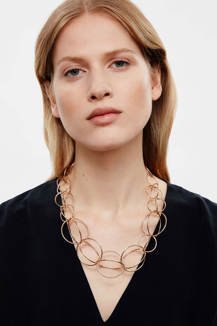 An interlocking, spherical design, this short necklace is made from shiny metal…