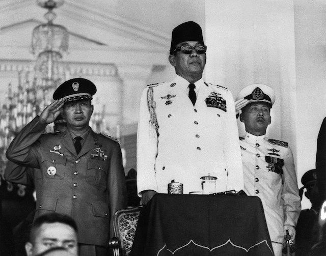 Presiden Soekarno (tengah) dan Letjen Soeharto (kiri) memberi hormat kepada bendera merah putih saat upacara kemerdekaan 17 Agustus 1966. Foto oleh AFP
